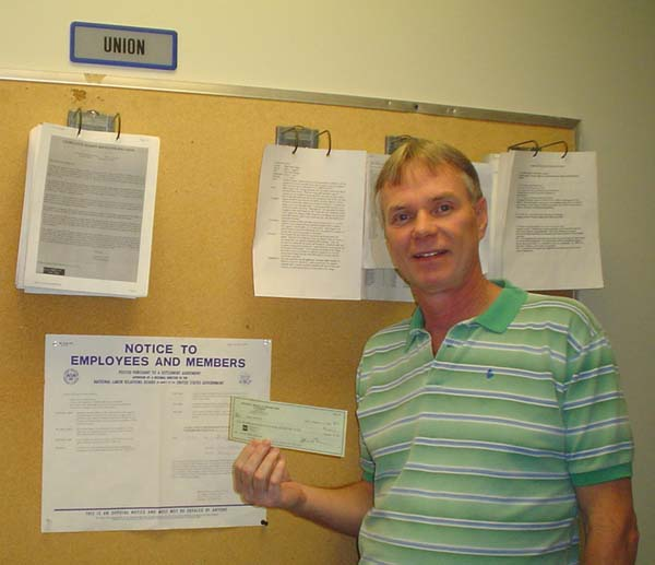 Randy holding his check in front of Federal Violation Notice
